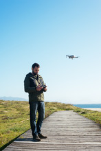 Young Man Flying A Dron Near T...