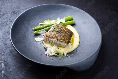 Obraz Traditionelles gebratenes Skrei Kabeljau Fisch Filet mit grünen Spargel Spitzen und Kartoffelpüree Creme in Parmesan Oliven Öl Sauce als closeup auf einem Modern Design Teller mit Textfreiraum - fototapety do salonu