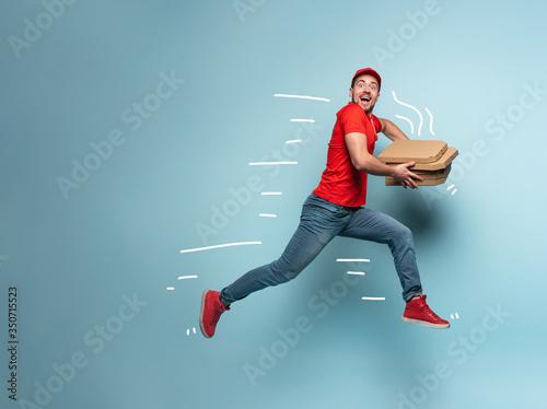 Fotografia, Obraz Courier runs fast to deliver quickly pizzas. Cyan background