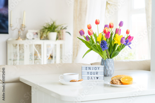 Fototapeta Good morning concept. Romantic breakfast - fresh spring flowers, cup of hot coffee drink, cookies, orange, lightbox with message Enjoy your day on marble table with light interior view. Copy space. obraz