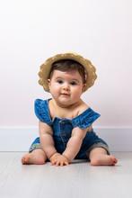 Niña Pequeña Jugando En Su Cubo Rosa, Con Un Peto Azul.