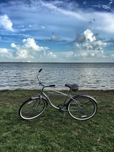 Bicycle Parked On Field By Sea Against Blue Sky At Alice Wainwright Park
