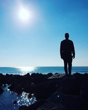 Silhouette Man Standing On Rock Formation At Sea Against Clear Sky During Sunny Day