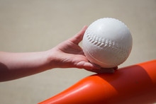 Child's Hand Holding A White Plastic Baseball Against A Red Bat