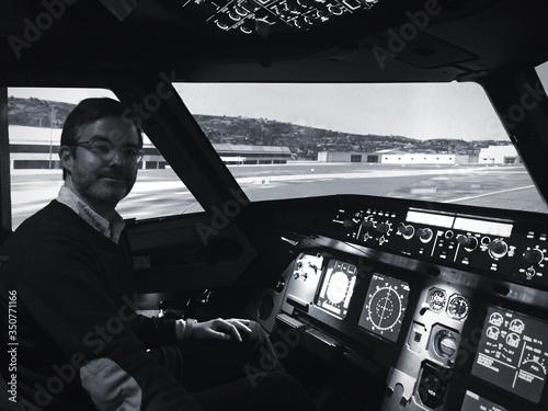 Fototapeta Portrait Of Mature Man Sitting At Cockpit In Airplane