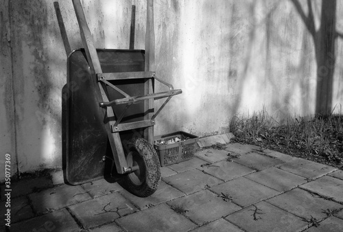 Billede på lærred High Angle View Of Wheelbarrow Leaning On Wall In Back Yard