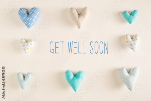 Get well soon message with blue heart cushions on a white paper background Tablou Canvas