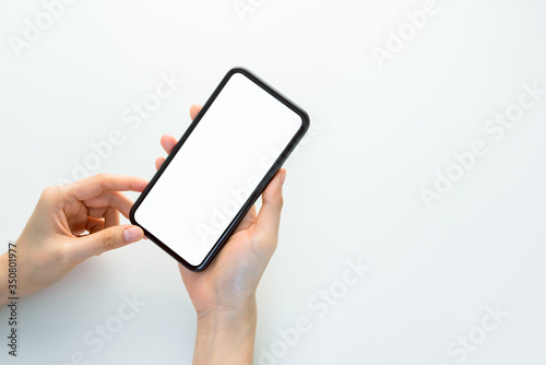 Fototapeta Hand holding smartphone mockup of blank screen on the table. Take your screen to put on advertising. obraz