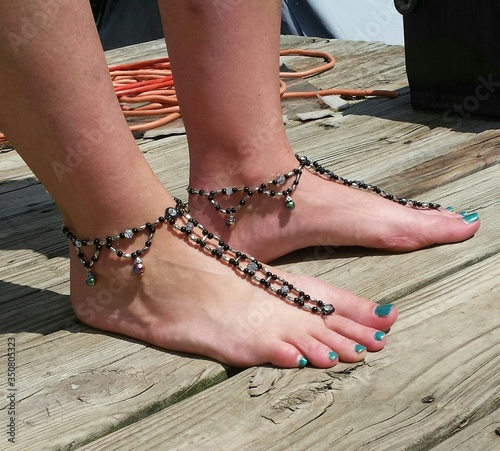 Photo Low Section Of Woman Wearing Hand Made Anklet On Wooden Plank