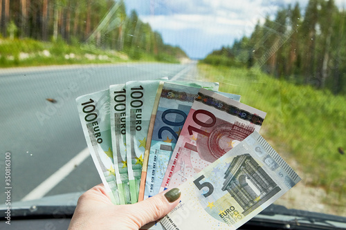 Fotomural Euro banknotes of various denominations in a woman hand inside of a car