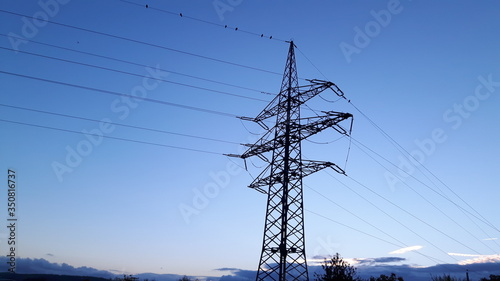 Fotografie, Obraz Low Angle View Of Electricity Pylon Against Clear Blue Sky