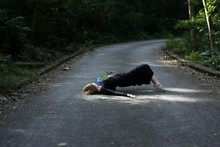 Woman With Flower Lying On Road