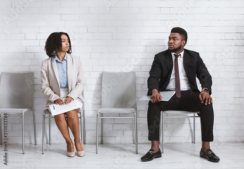 Photo Male and female vacancy candidates looking at each other with antipathy while wa