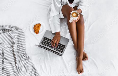 African american girl typing on laptop and holding coffee, near croissant on plate