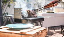 Chef Grill T-bone Steak At Barbecue Sunday Lunch Outdoor - Man Cooking Meat For A Family Bbq Meal Outside In Backyard Garden - Summe Lifestyle And Bbq Food Concept - Focus On Tongs, Hand