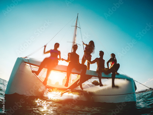 Canvas Silhouette of young friends chilling in private catamaran boat - Group of people