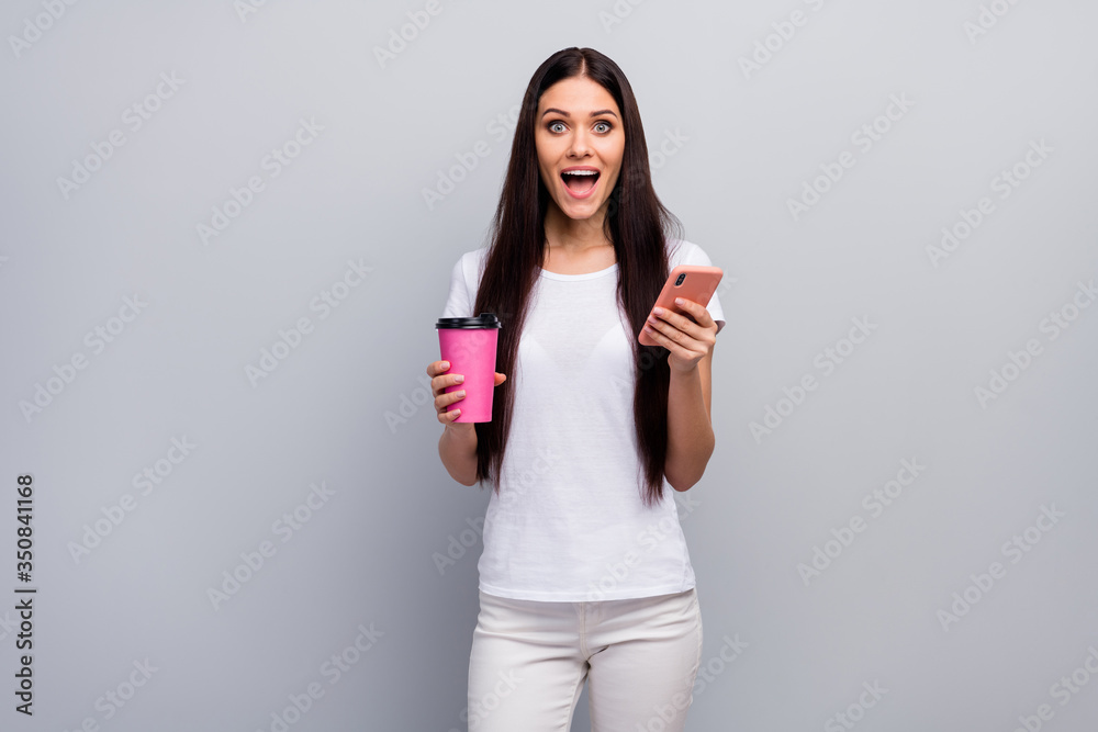 Fototapeta Portrait of her she nice attractive lovely lovable amazed cheerful straight-haired girl holding in hands using cell drinking latte having fun isolated over light gray pastel color background