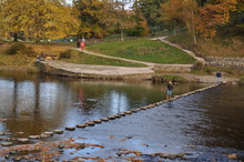 People Standing On Stepping Stone Amidst River At Bolton Abbey