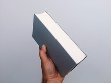 Cropped Hand Holding Book Against Gray Background