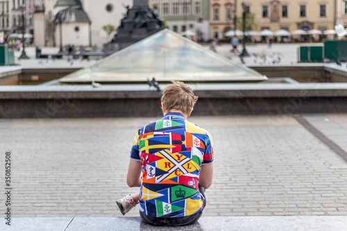 Fototapeta Man in a colorful polo sitting on the bench