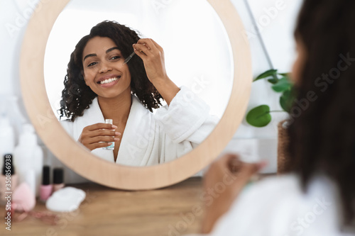 Obraz Skin nutrition. Beautiful black woman applying moisturizing serum on face at home - fototapety do salonu