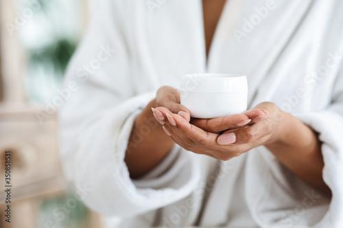 Fényképezés Jar of nourishing cream in hands of unrecognizable black woman in bathrobe