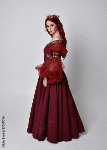 Portrait of a beautiful woman with red hair wearing  a  flowing Burgundy fantasy gown and golden crown Wallpaper Mural