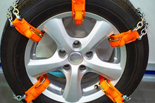 Wheel With Antiskid Chains Close-up. Chains And Anti-slip Belts On The Wheels Of The Car. Devices For Improving The Coupling Properties Of Wheels On Ice. Anti-slip Equipment For Car.