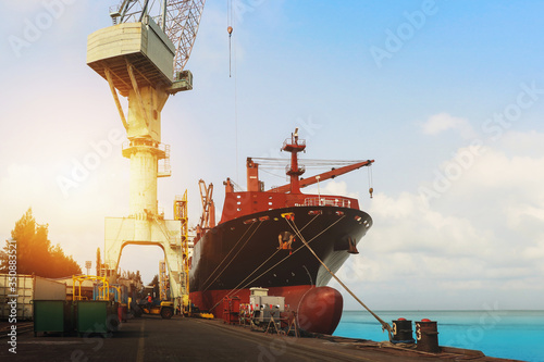 Fotomural Shipyard Ship Repair, front view of Cargo ship Moored in port, quawall and tower crane lifting during waiting go to on floating dry dock