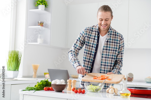 Fototapeta Portrait of positive cheerful gourmet guy enjoy proper nutrition weekend cook fresh salad add sliced tomato wear casual checkered plaid shirt in kitchen house indoors obraz