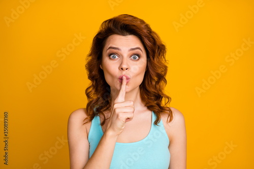 Fototapeta Shh. Closeup photo of pretty sly foxy wavy lady hold finger on lips tricky mood arrange surprise party for friends wear teal casual tank-top isolated bright yellow color background obraz