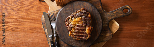 Fotografía top view of tasty grilled steak served on wooden board near cutlery, panoramic s