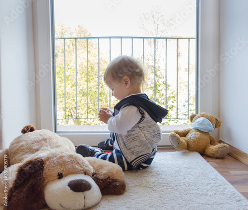 Child in home quarantine playing at the window with his toys, sick teddy bear wearing a medical mask against viruses during coronavirus and flu outbreak.Children and illness COVID-2019 disease concept