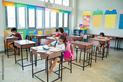 Obraz Group of school kids wearing protective mask to Protect Against Covid-19 with teacher sitting in classroom,education,elementary school,Social Distancing,learning and people concept. - fototapety do salonu
