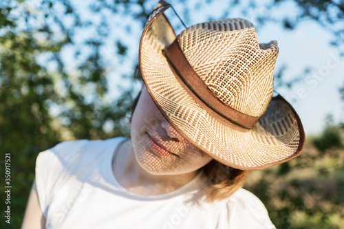 close up image of young female in straw hat with hidden eyes and sun reflection from straw grid  on face Billede på lærred