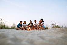 Group Of Young Friends Sitting On Beach And Fry Sausages. One Man Is Playing Guitar. Summer Holidays, Vacation, Relax And Lifestyle Consept. Camping Time.