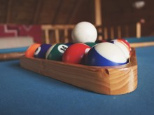 Close-up Of Pool Balls In Wooden Triangle On Table