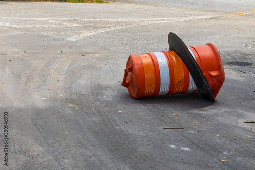 фотографія Orange and white traffic barrel knocked over on its side, traffic accident reckl