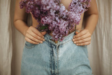 Woman Posing With Lilac Branches In Denim Jeans On Rustic Background. Blooming Lilac Flowers Covering Naked Upper Body. Creative Moody Image. Sensuality And Tenderness Concept
