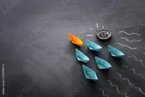 Obraz na plátně Leadership banner concept with paper boat on blackboard background