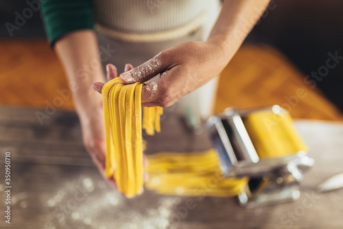 Obraz Closeup of process of making cooking homemade pasta. Woman make fresh italian traditional pasta. - fototapety do salonu