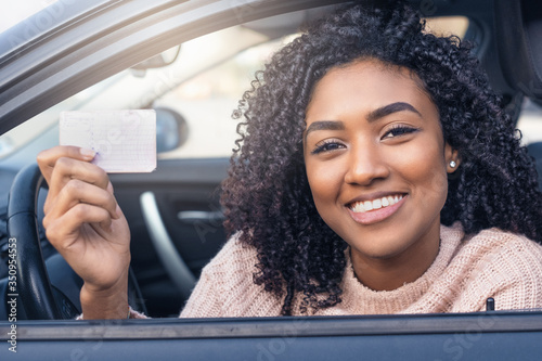 Cuadros en Lienzo Young black woman at the wheel showing driving license