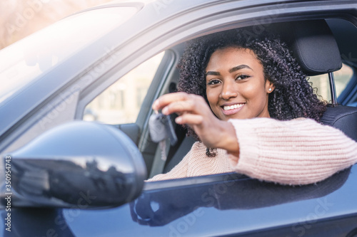 Obraz Young black woman at the wheel on her new car - fototapety do salonu
