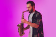 Leinwandbild Motiv Young caucasian jazz musician playing the saxophone on gradient pink studio background in neon light. Concept of music, hobby, festival. Joyful, cheerful attractive guy. Colorful portrait of artist.