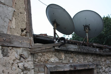 Satellite Dish On The Roof Of An Abandoned House