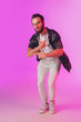 Leinwandbild Motiv Young caucasian musician, dancer, partyhost isolated on gradient pink studio background in neon light. Concept of music, hobby, festival. Joyful, cheerful attractive guy. Colorful portrait of artist.