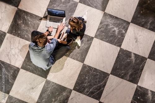 Famiglia felice e seduta nel pavimento mentre il papa usa il computer Canvas-taulu