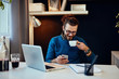 Young attractive bearded hipster sitting in his office, drinking coffee and using smart phone.