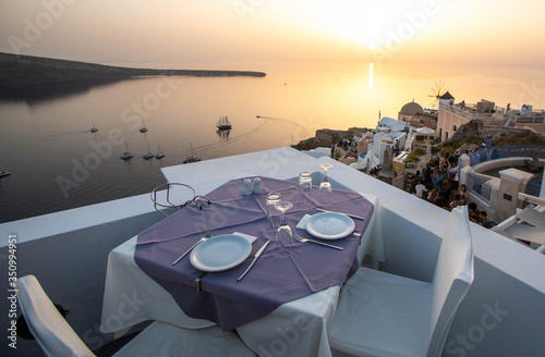 Fotografie, Obraz table and chairs near the beach, sunset at santorini