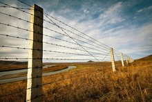 Barbed Wire Fence On Grassy Field Against Sky